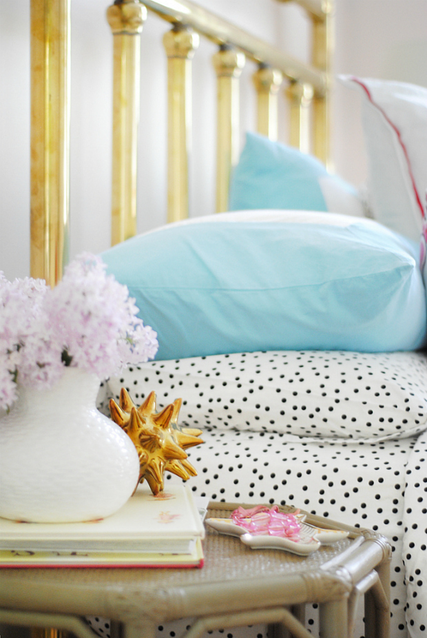 Brass headboard with aqua, pink, black, and white