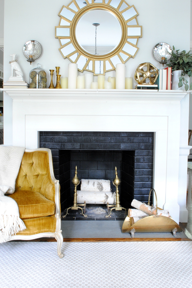 Simple fall mantle with dried artichokes, eucalyptus branches, books, gold accents, and classic white candles
