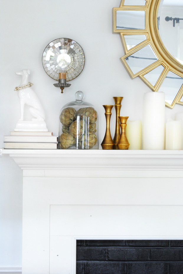 Fall mantle with white dog statue, dried artichokes, brass candlesticks