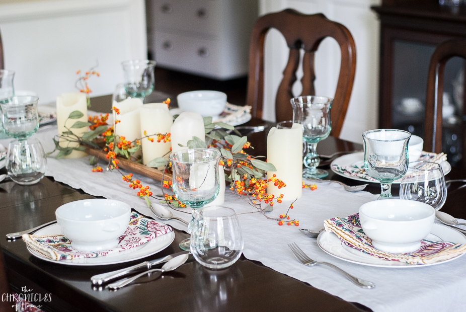 Simple table setting using branches, white dishware, and colorful napkins