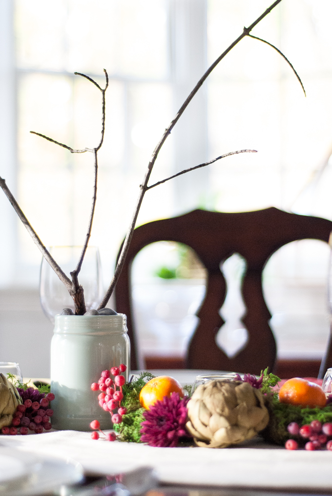 A jewel toned Thanksgiving tablescape with moss, artichokes, clementines, mums, and bare branches. Fresh, chic, and dramatic but still so simple to assemble!