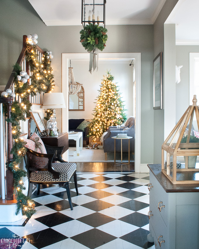 Stunning classic Christmas entryway - painted black and white checkered floors, garlands, twinkle lights, and a gorgeous, traditional tree
