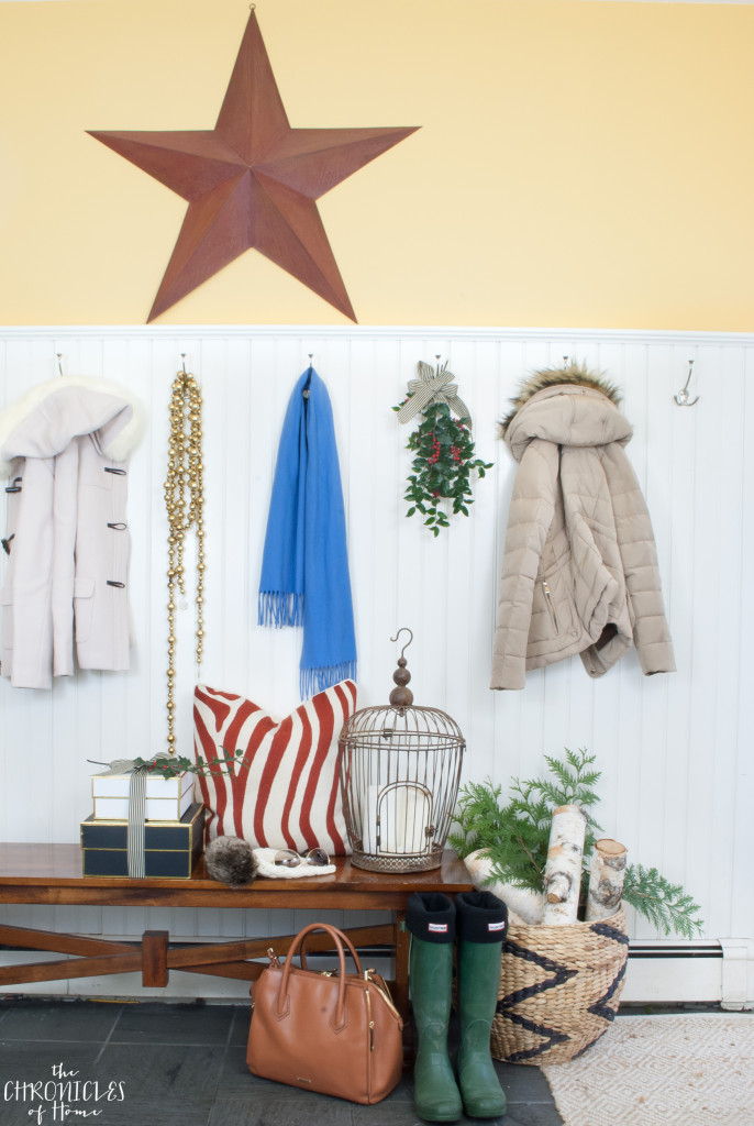 A Christmas mudroom with red barn star, greenery, and firewood