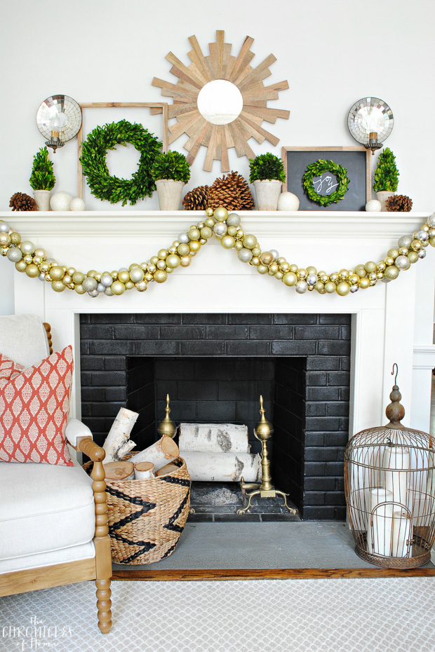 Christmas mantle with boxwood, pinecones, natural wood, and gold ornaments. Classic, natural, and glam.