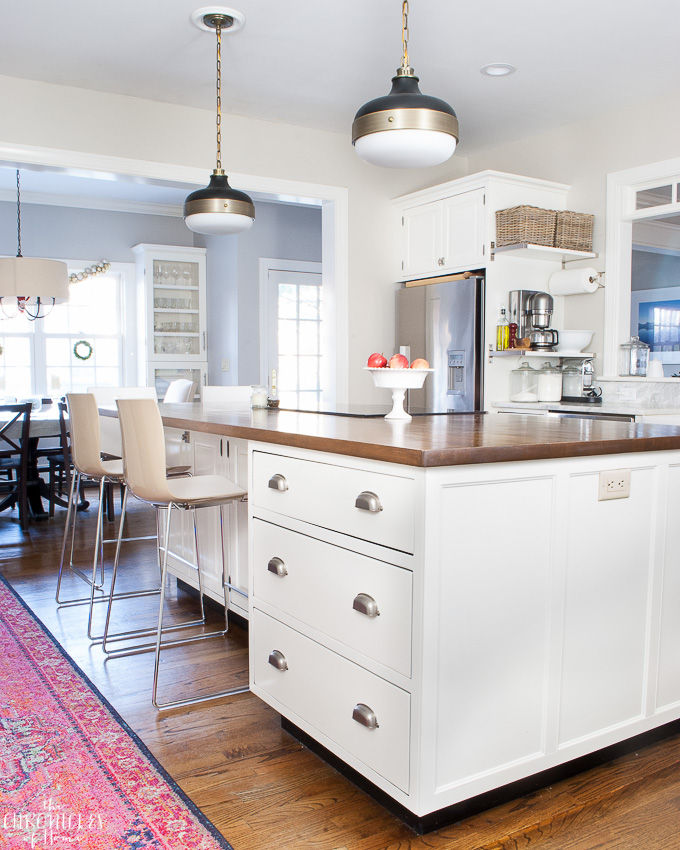 white traditional white kitchen, brass and black pendants, modern two-tone kitchen stools