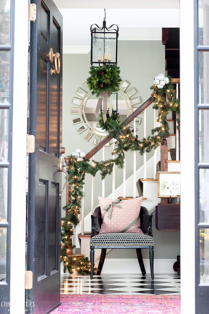 A classic Christmas entryway with black front door, garlands, twinkle lights, and a kissing ball hung from the lantern