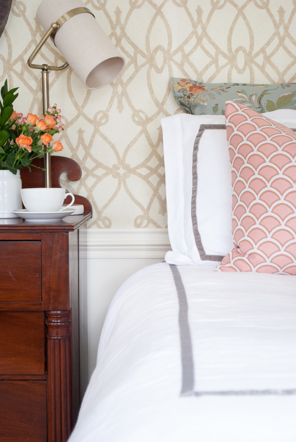 Classic bedroom with white duvet, soft graphic wallpaper, dusty blue and blush accents.