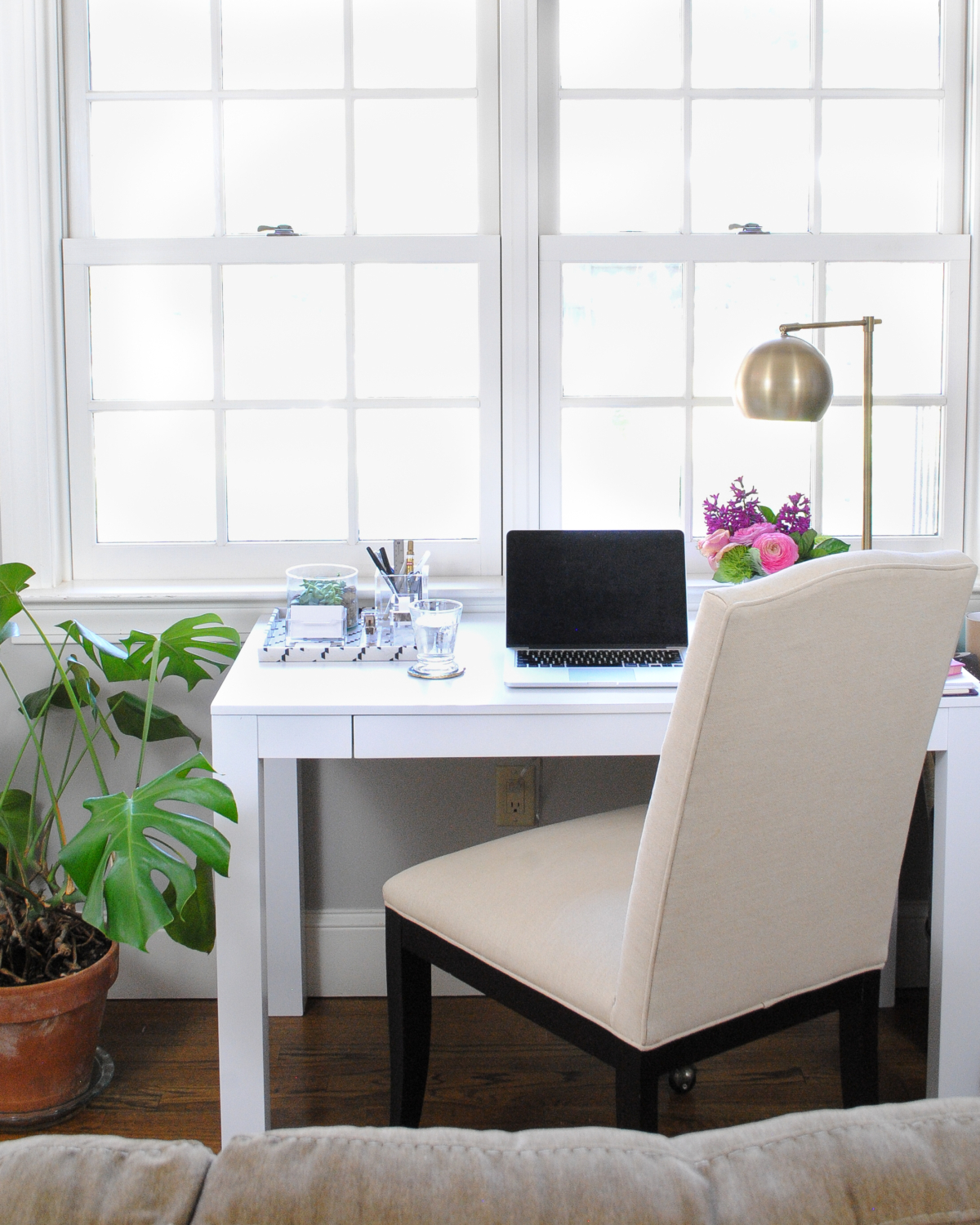 Pretty desk nook with white parsons desk, brass task lamp, lucite and gold accessories
