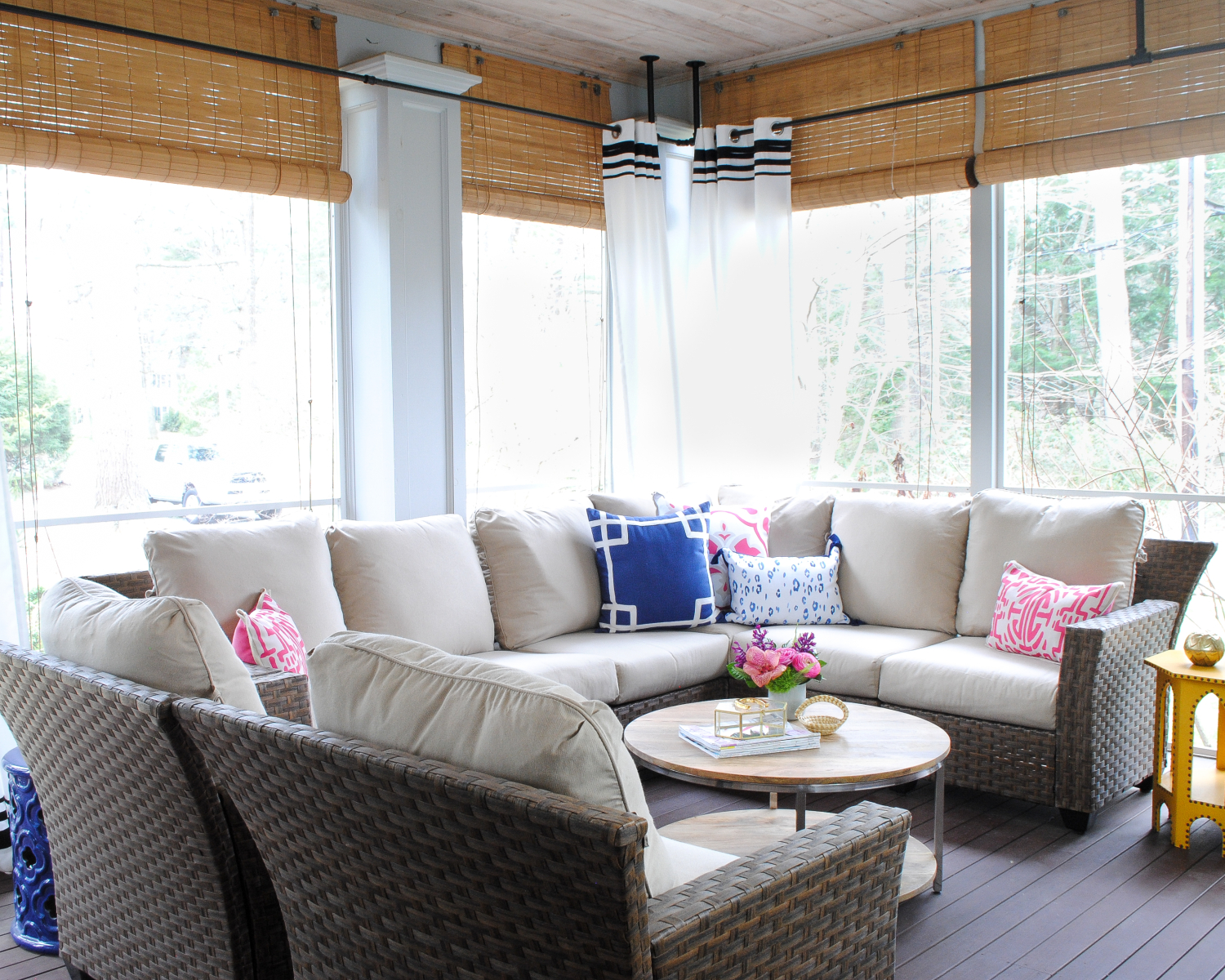 Delightful Screened Porch With Woven Wicker, Round Coffee Table, Navy Blue And Pink  Accents