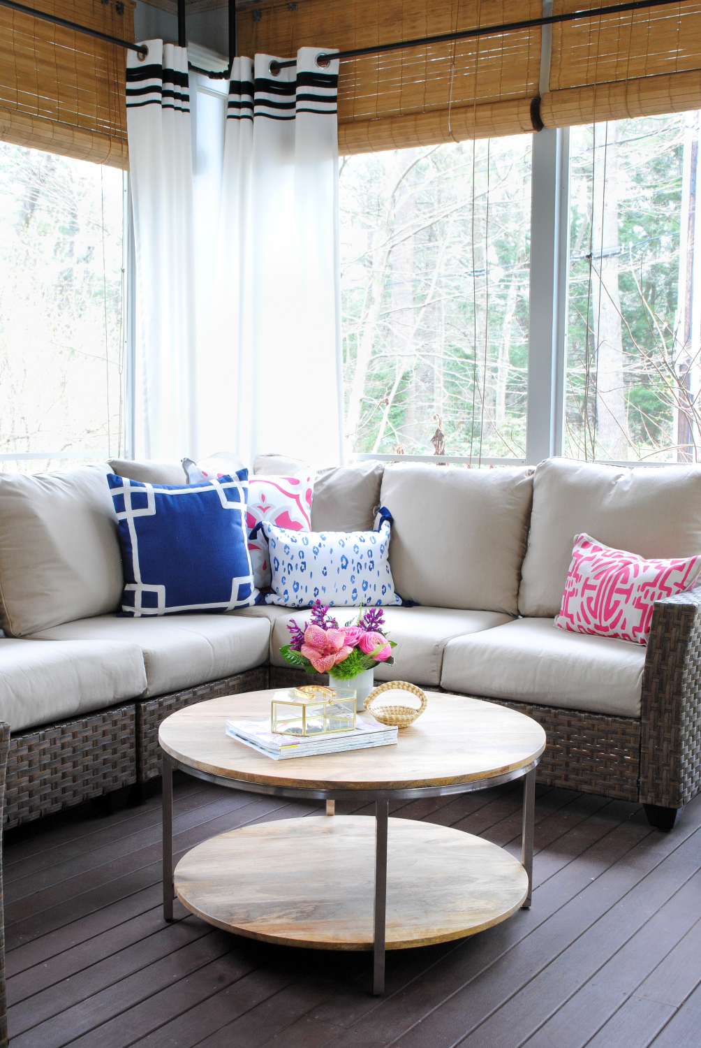 Nice Screened porch with woven wicker round coffee table navy blue and pink accents