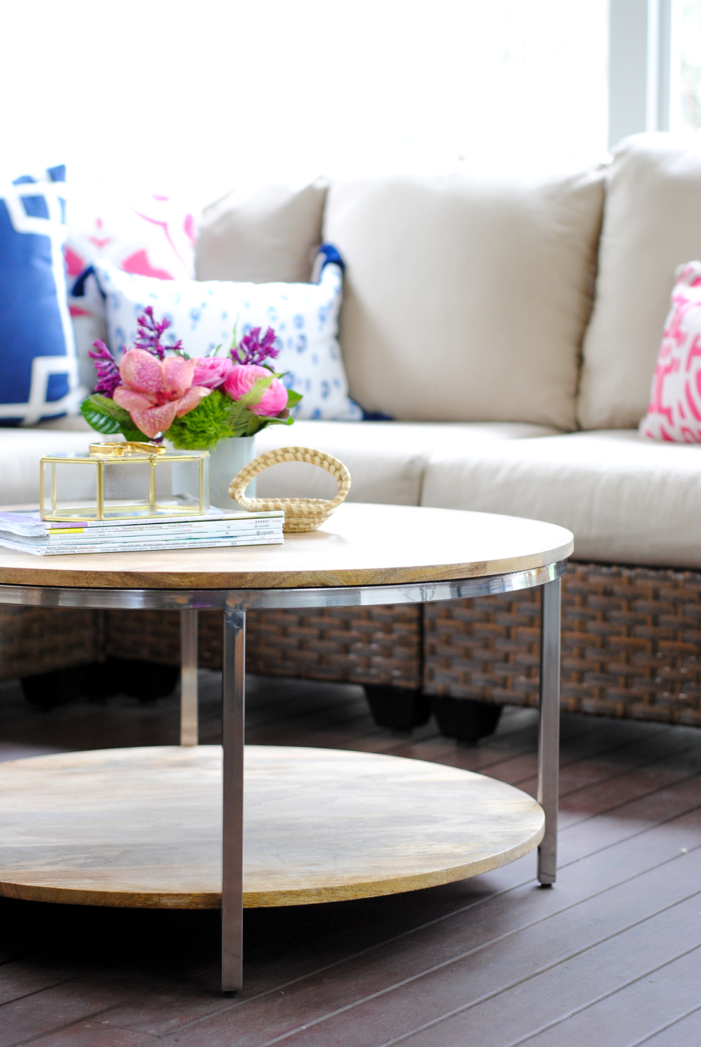 Screened Porch With Woven Wicker, Round Coffee Table, Navy Blue And Pink  Accents