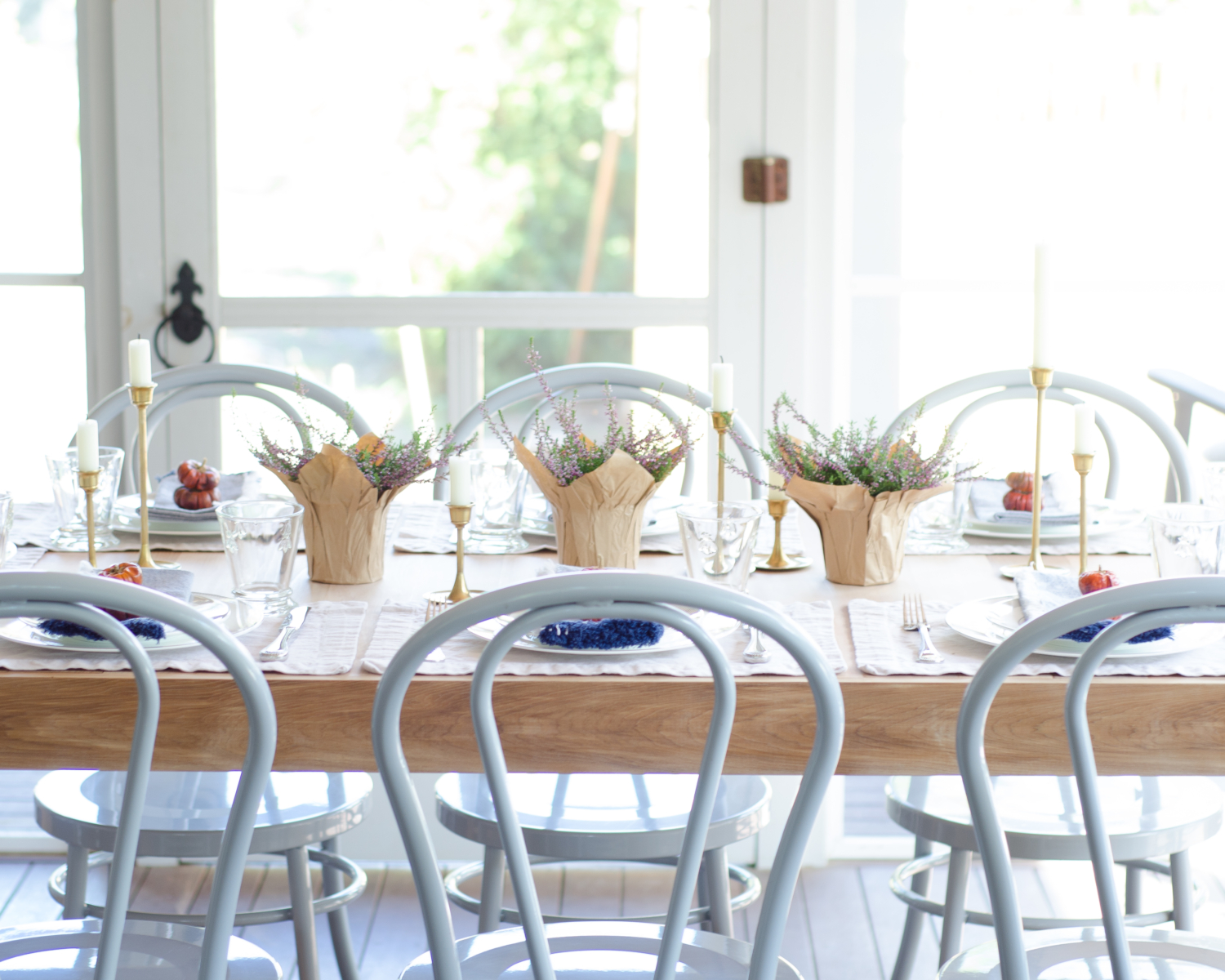 Fall outdoor dinner party with a simple table with mini pumpkins, brass candlesticks, and miniature flower pots. Metal bentwood chairs are perfect for light outdoor use!
