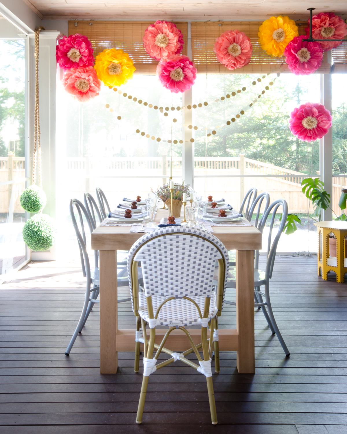 Fall outdoor dinner party with paper flowers, gold circle garlands, and a simple table with mini pumpkins, brass candlesticks, and miniature flower pots.