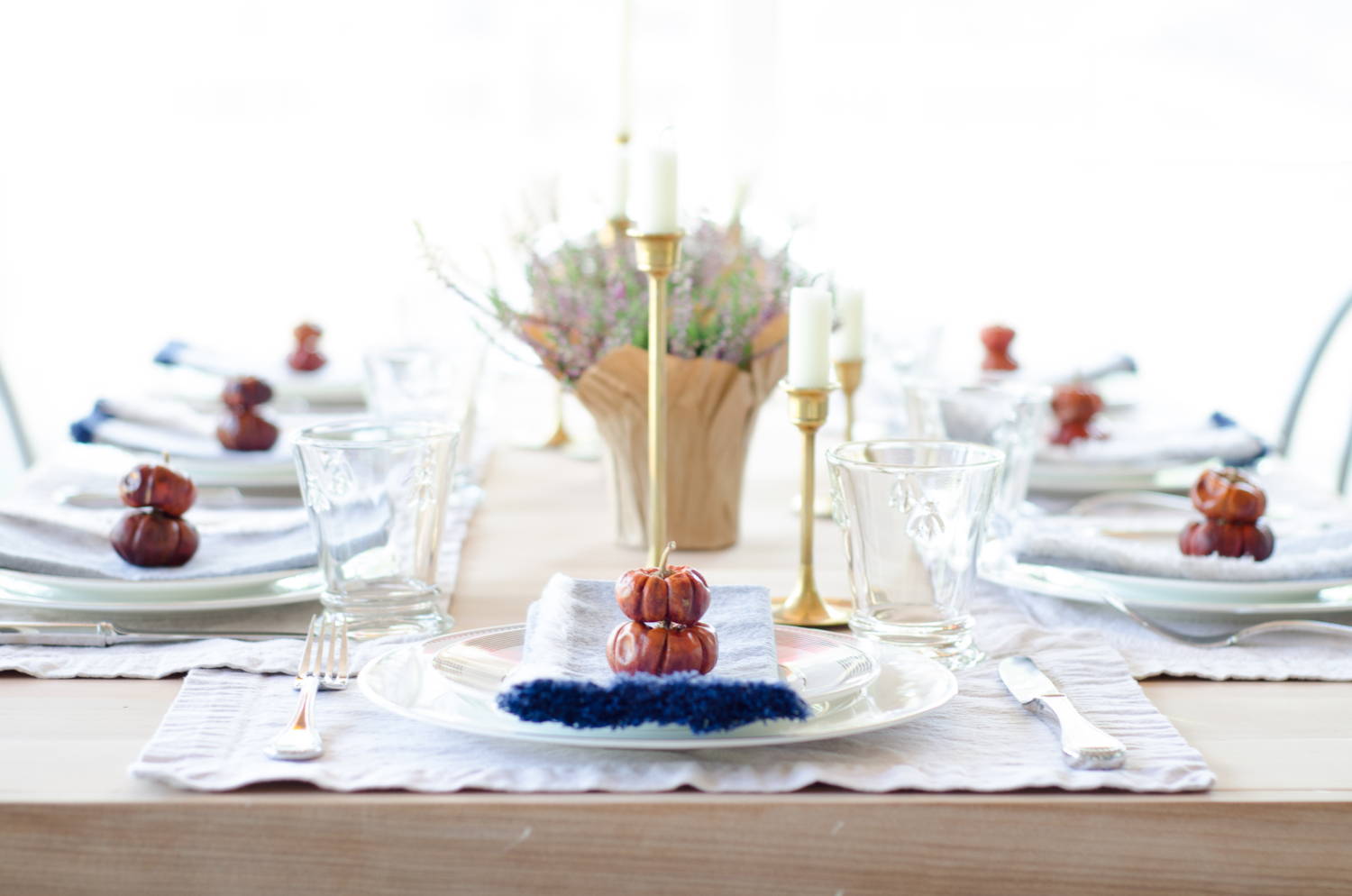 Simple, classic fall table with brass, navy blue, white, purple, and deep orange.