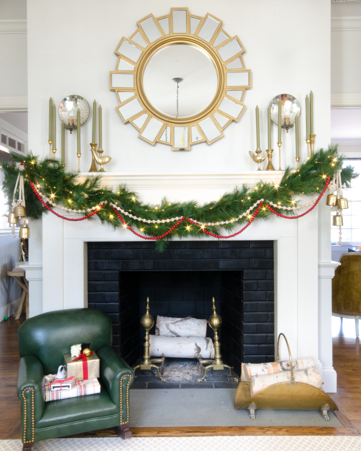 Classic Christmas mantle with greenery garland, red beads, and gold bell clusters.