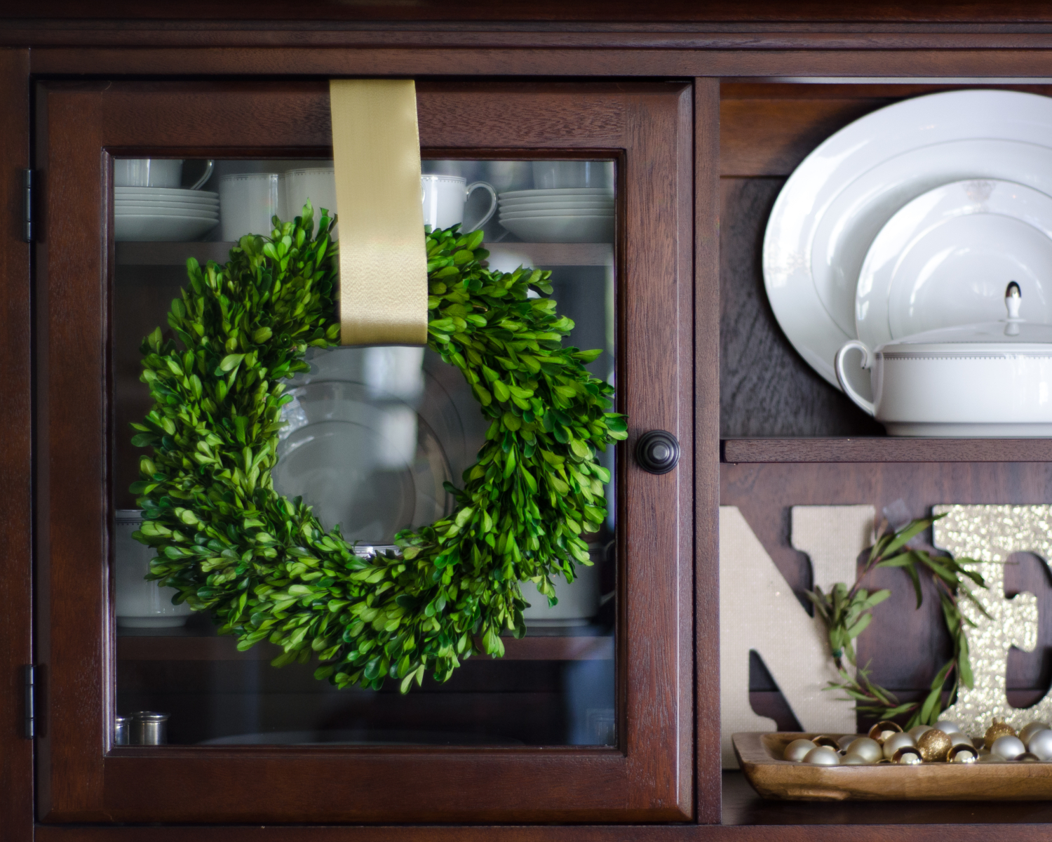 Boxwood wreaths hung on a dining room hutch for Christmas