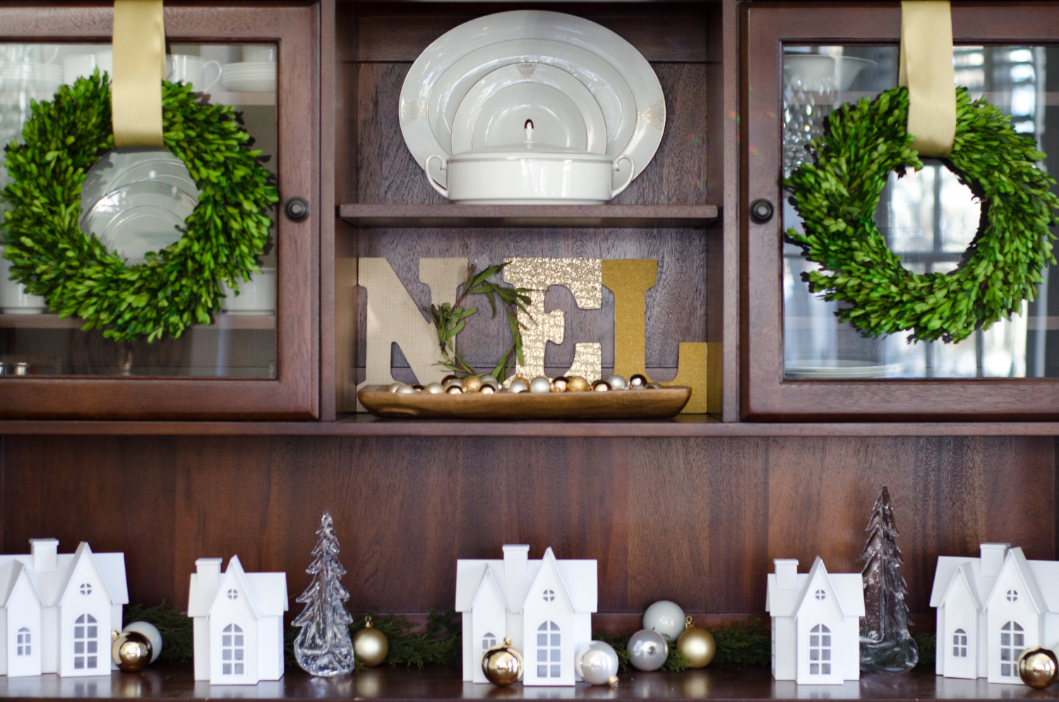 Christmas dining room with boxwood wreaths, Noel display, and a Christmas village scene
