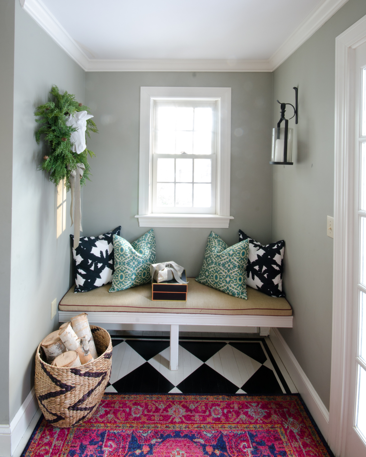 Classic Christmas entryway with greenery, twinkle lights, cable knit stockings, and more! So much inspiration!!