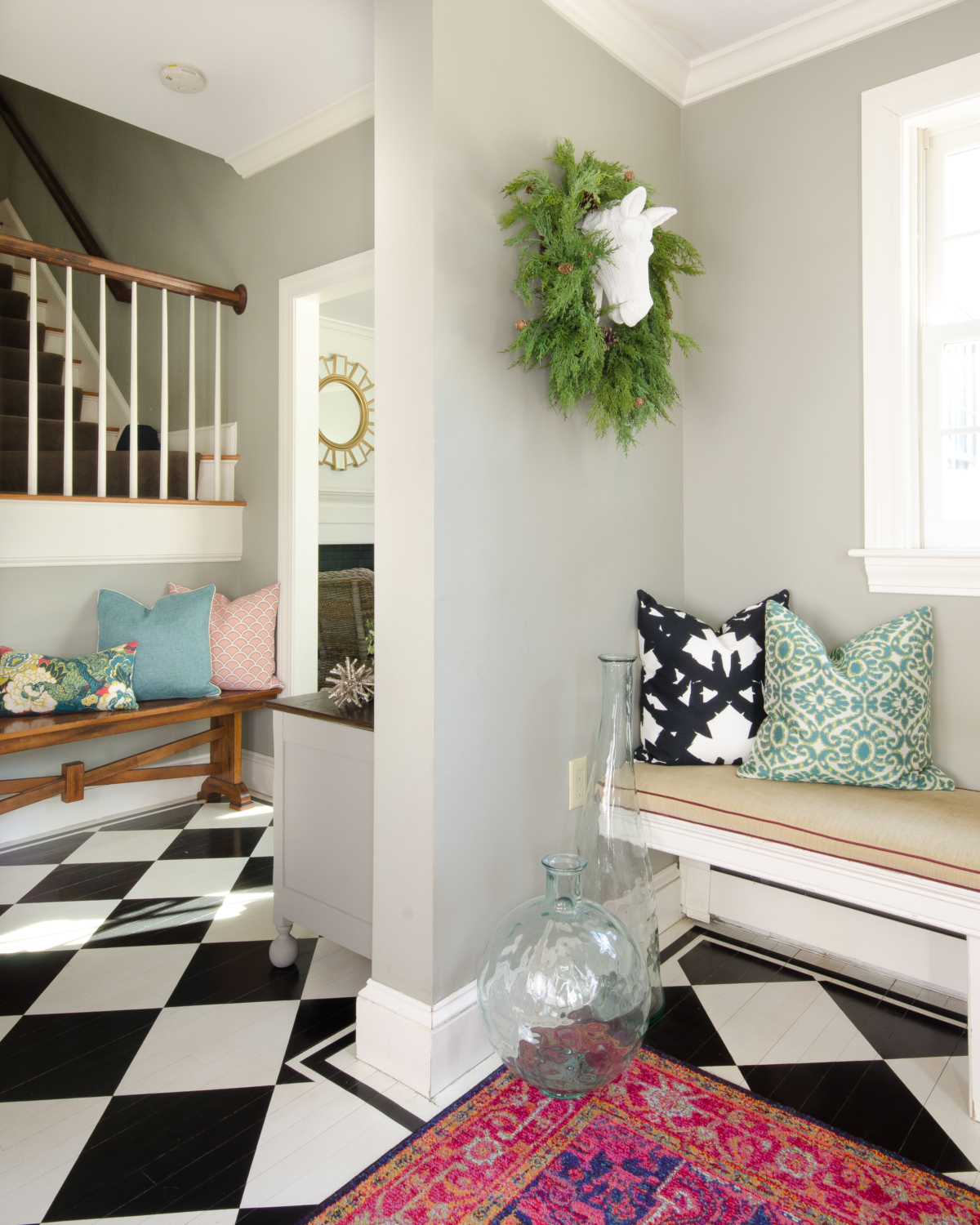 A charming, fresh entryway design featuring black and white, deep pink, and teal blue accents.