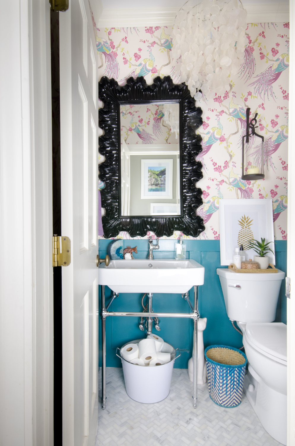 A small powder room gets a majorly gorgeous makeover, including marble tile, console sink, bird wallpaper, and capiz shell pendant. You won't believe this before and after!