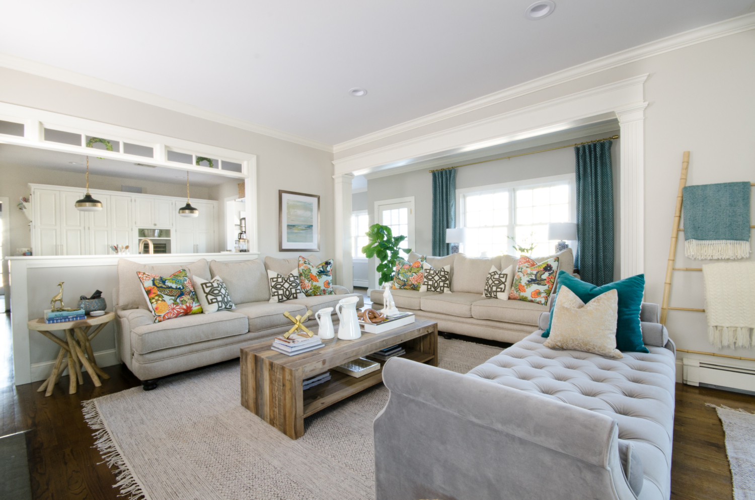 A stylish family room that's both chic and family-friendly featuring neutral furniture and thoughtful pops of color. Features an oversized English roll arm sofa, a tufted daybed / backless sofa that divides the room into two seating areas, and reclaimed wood accent tables to balance traditional and rustic.