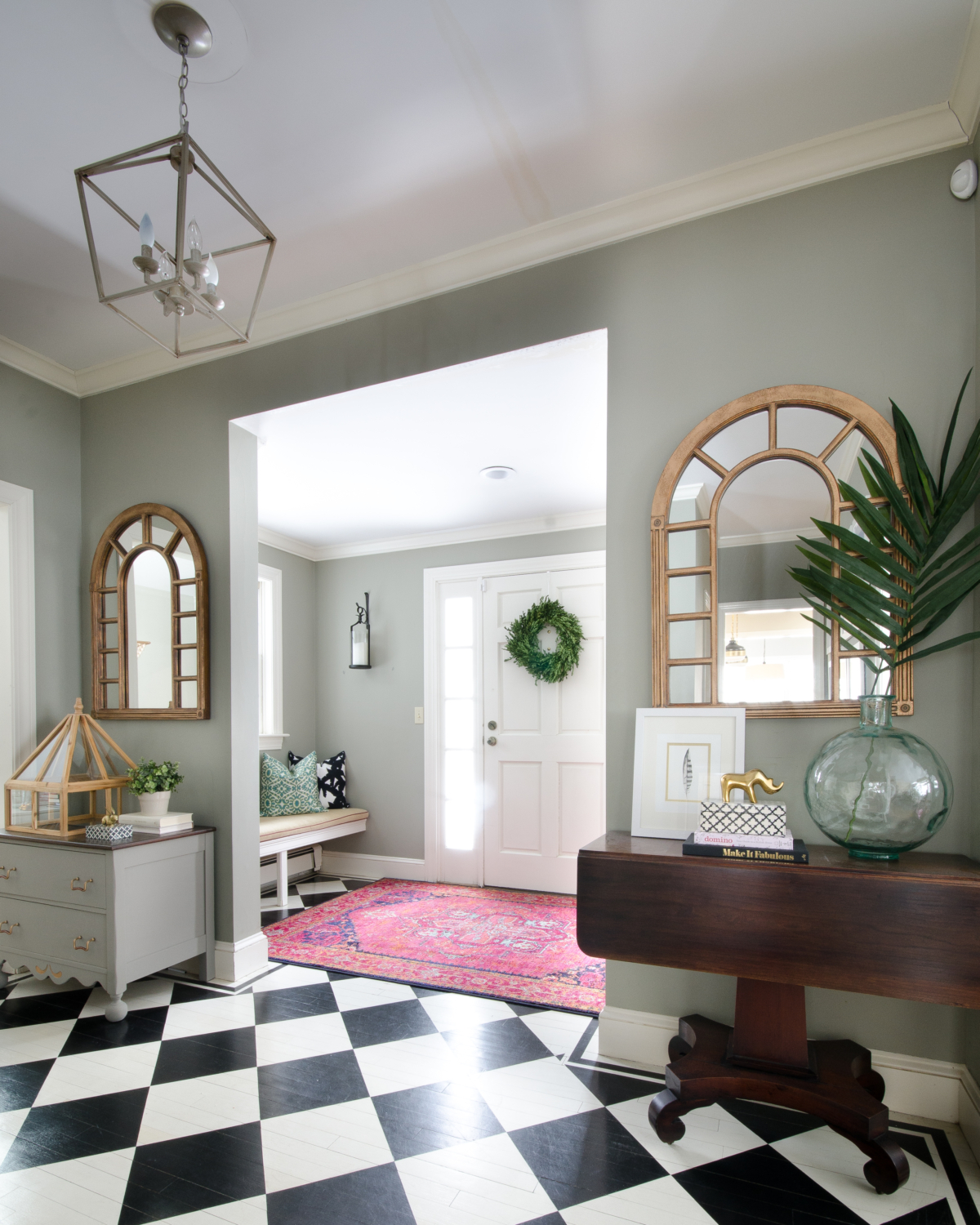 Entryway with built in bench seat, black and white checkered floors, pink rug, gold arched mirrors