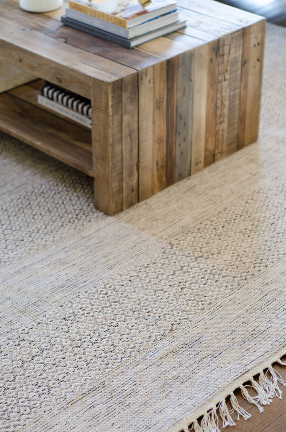 A family friendly rug made of flat weave cotton is shades of beige and grey.