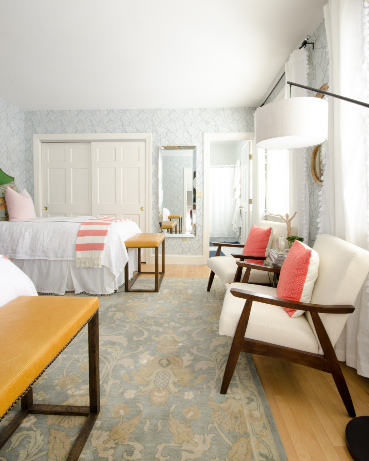 Gorgeous guest room with palm wallpaper, green linen headboards, mustard yellow leather benches, and accents of blush and coral