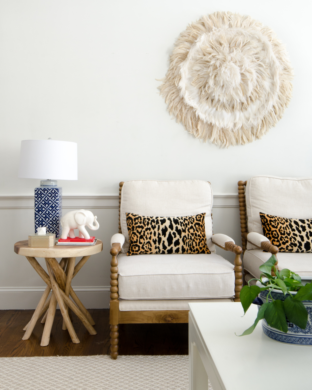 DIY feather wall hanging juju hat, spool chairs, Braemore Jamil Natural leopard pillows, rustic branch table