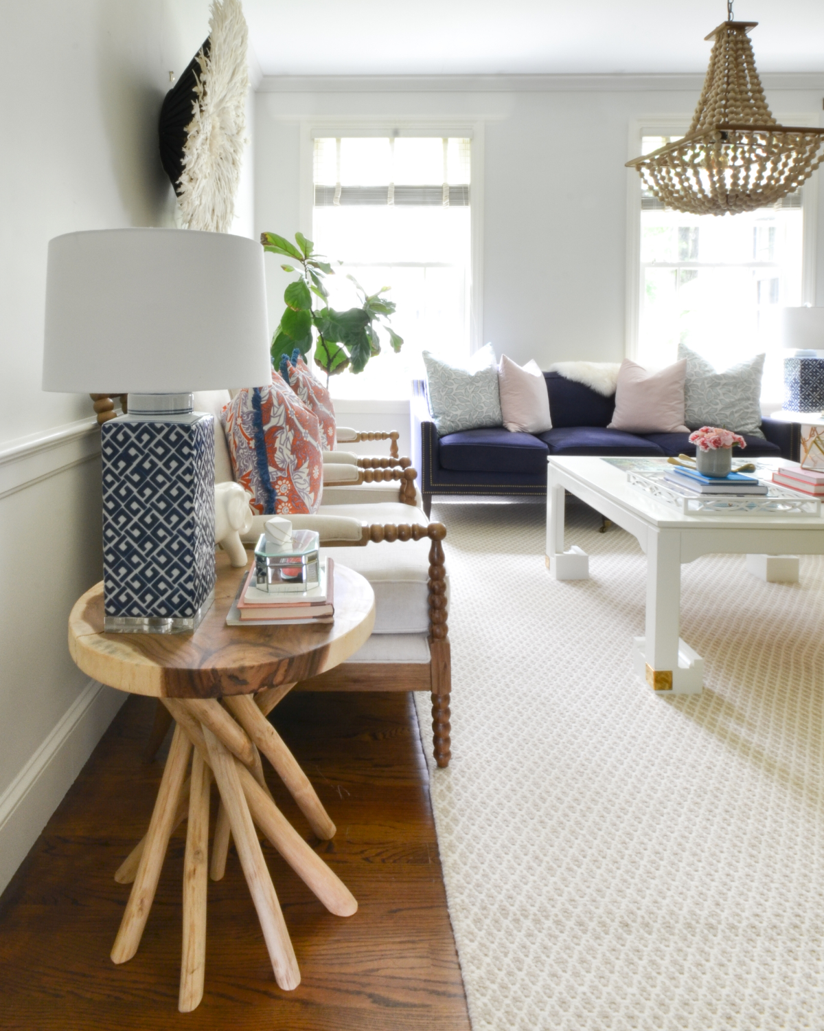 Living room with a neutral base, gold, navy blue, coral. Juju hat feather wall hanging is a striking centerpiece.