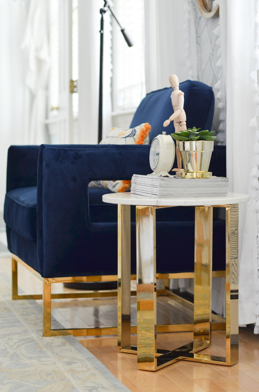 Navy blue velvet chair with brass and marble side table