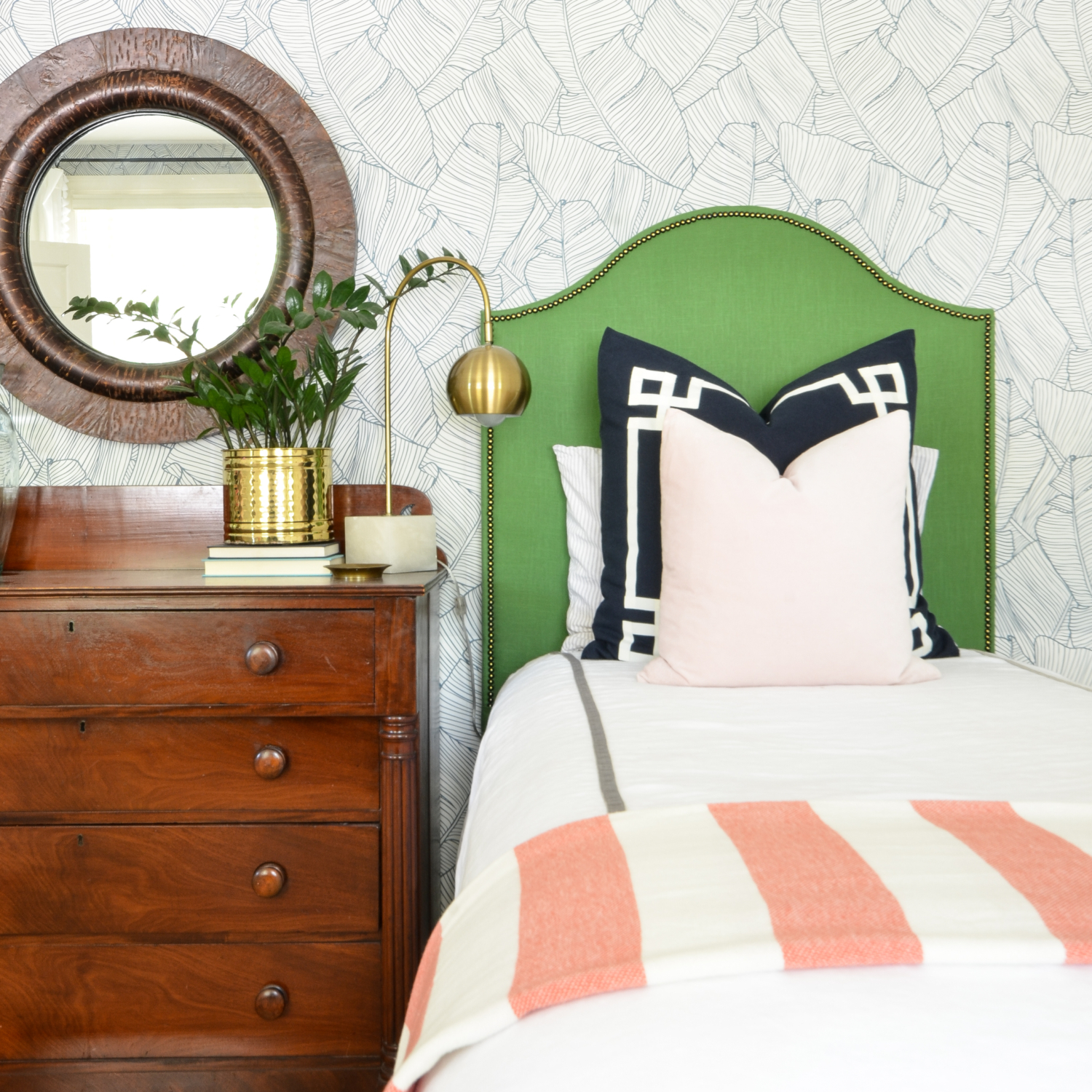 Wallpapered bedroom with twin beds, green upholstered headboards, navy blue, brass, and coral accents