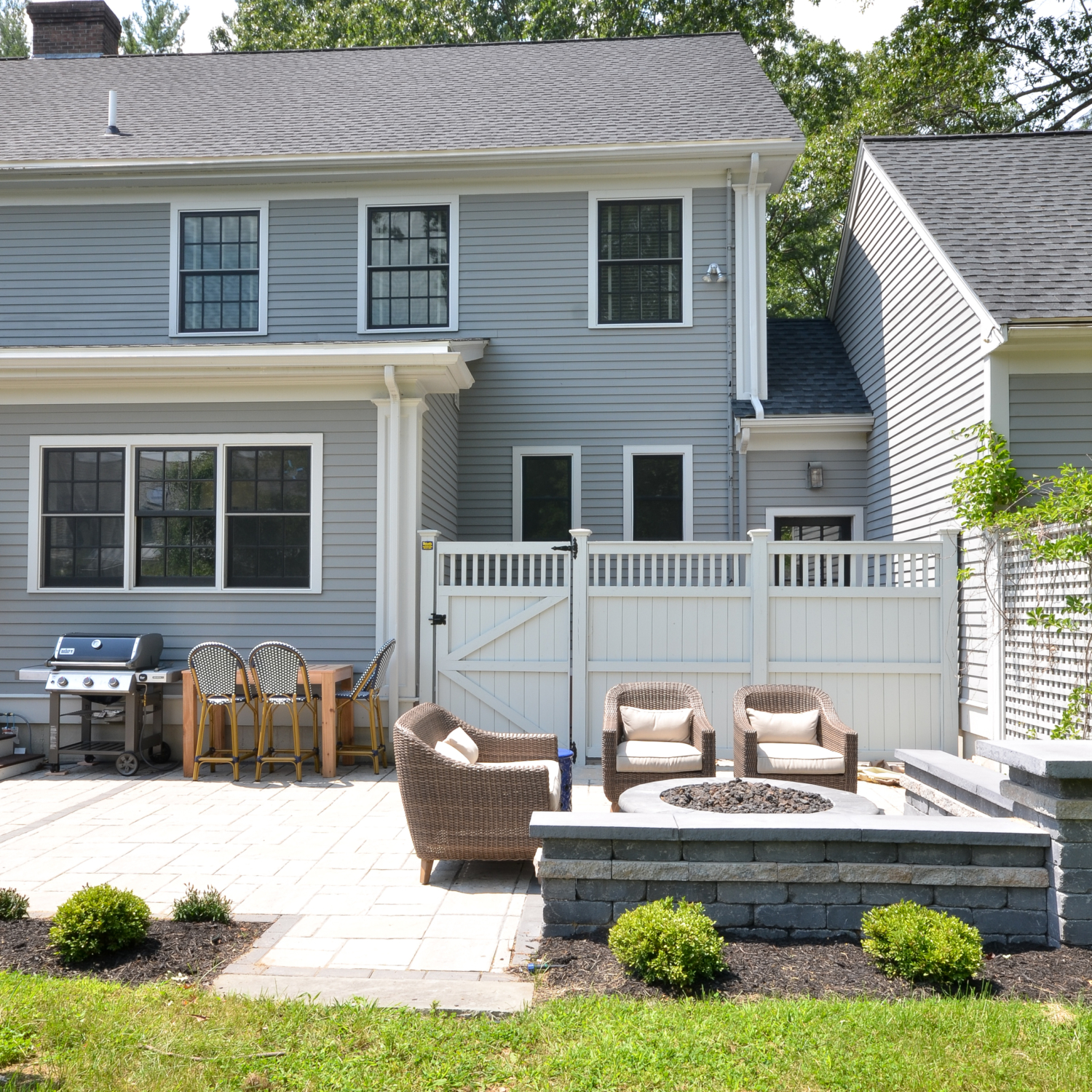 Amazing backyard landscaping makeover that includes a Trex deck, a paver patio with gas firepit, and a paver patio with a fountain and benches. So much outdoor inspiration!