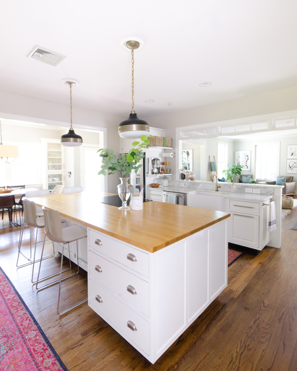 Classic white kitchen with butcher block counter and pendants similar to the Hicks pendant but way more affordable! Transom windows divide the kitchen and family room. Perimeter counter is quartzite that looks like marble!