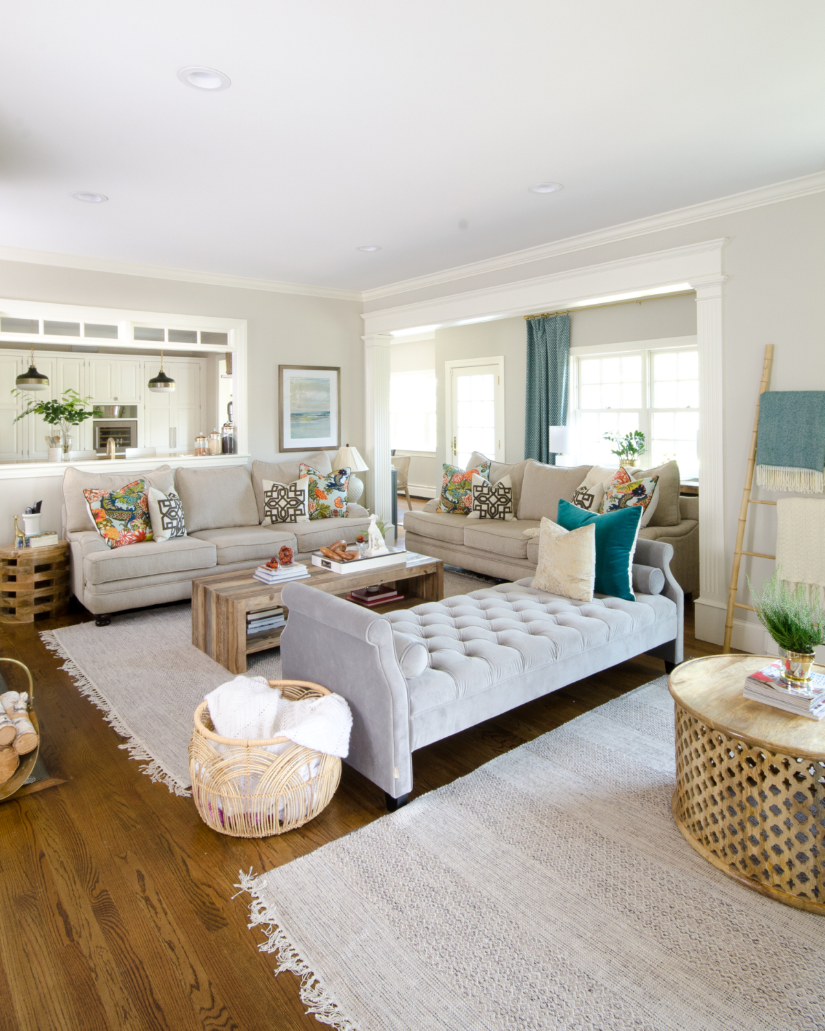 Beautiful neutral family room with pops of color and wood accents. Backless sofa divides the long room into two seating areas. Nice mix of traditional and rustic styles. Transom windows between the family room and kitchen.
