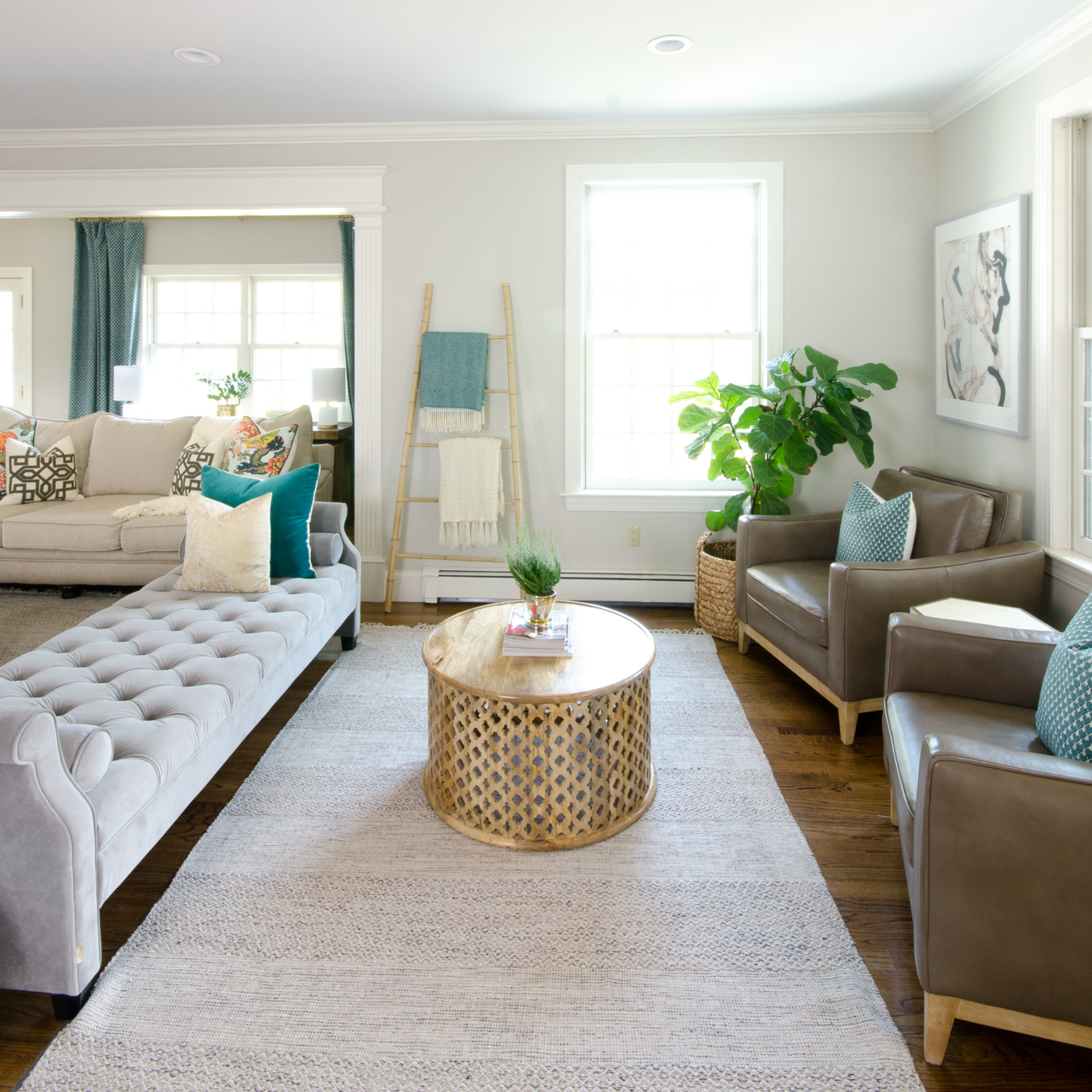 Beautiful neutral family room with pops of color and wood accents. Backless sofa divides the long room into two seating areas. Nice mix of traditional and rustic styles.