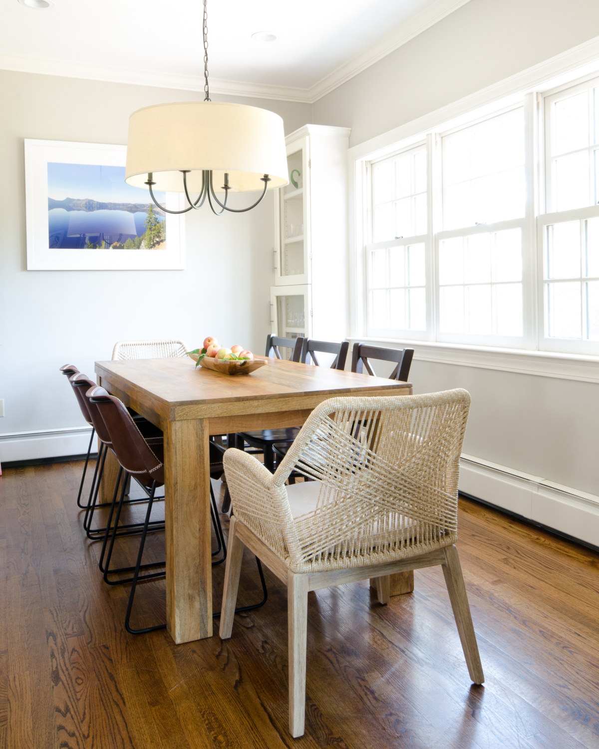 Pretty, neutral breakfast nook with farmhouse table, rope armchairs, and leather side chairs