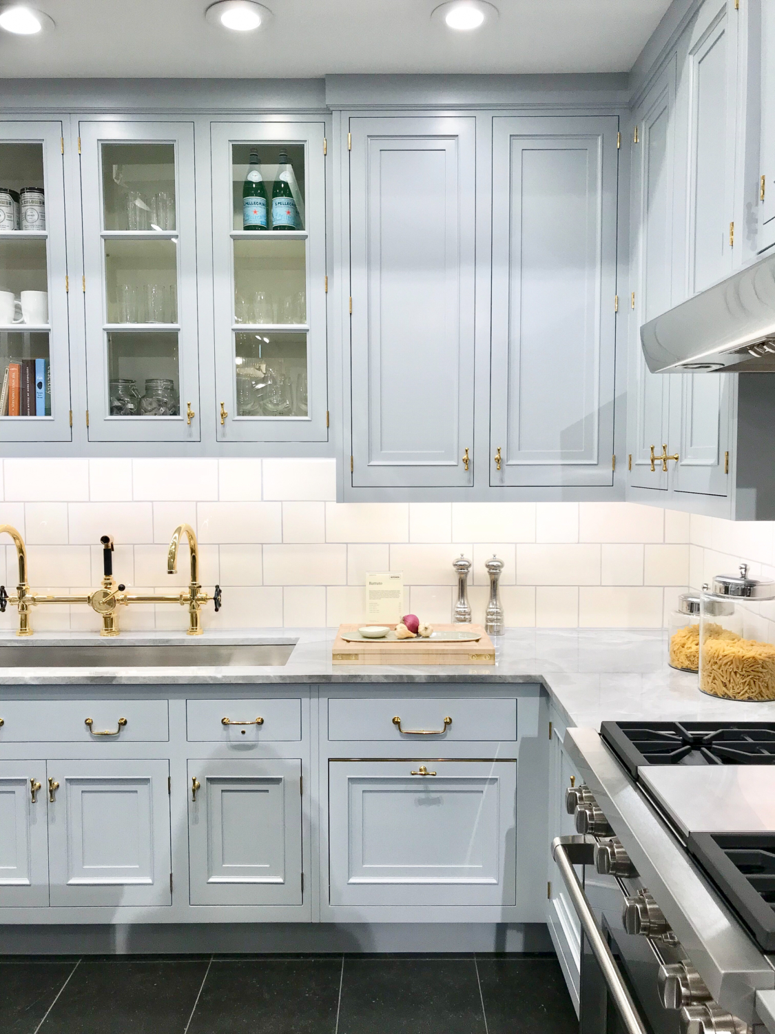 Grey kitchen cabinets with polished brass hardware