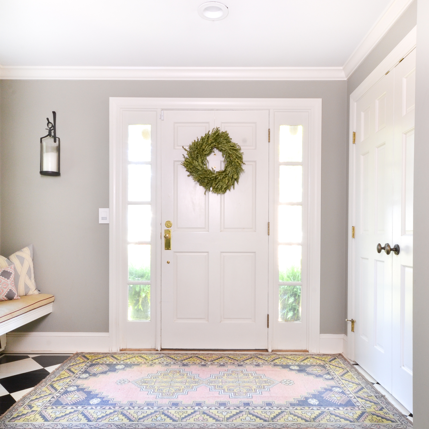Soft and feminine entryway with vintage rug and brass door hardware