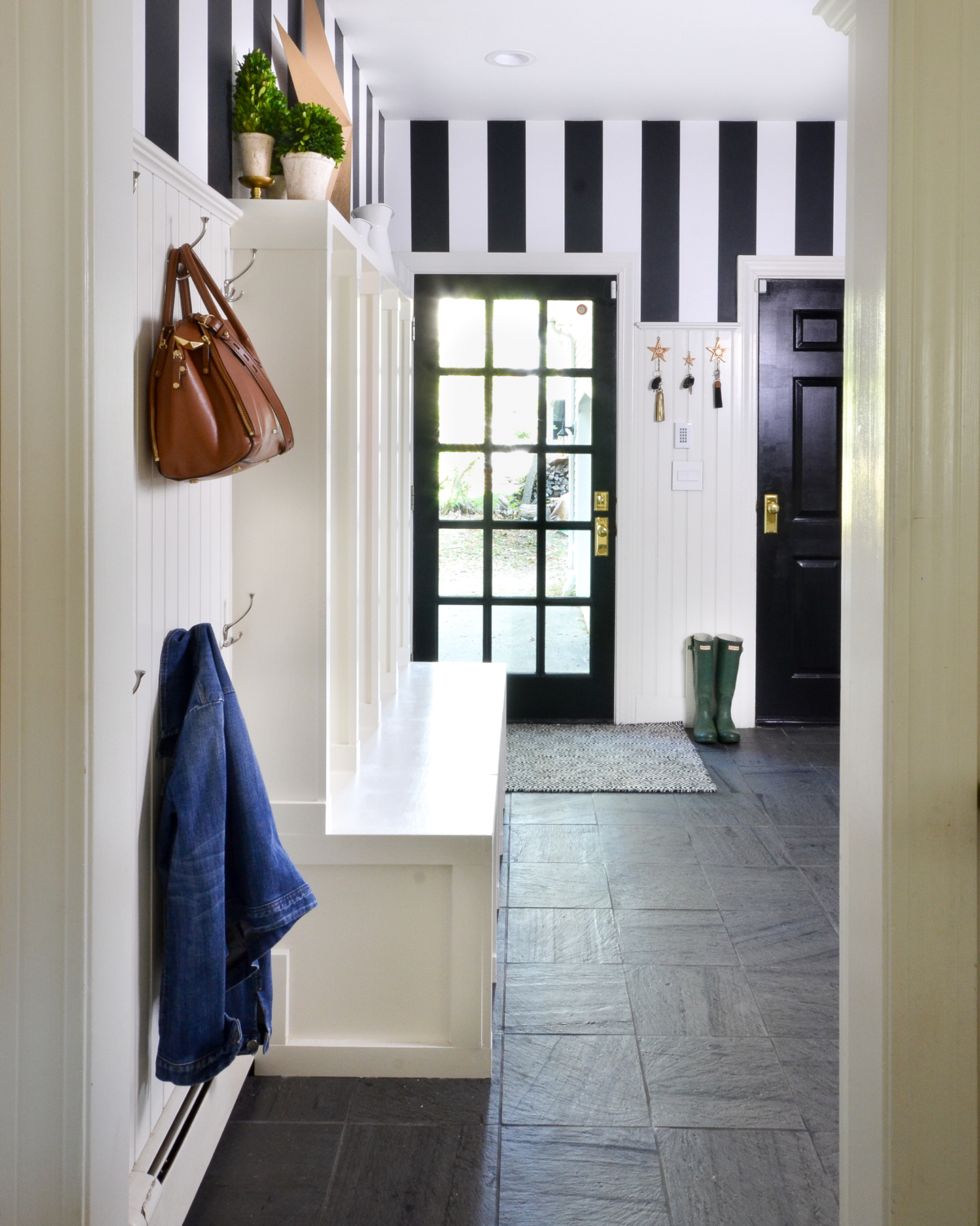 Black and white mudroom with striped wallpaper, beadboard, custom cubbies, black doors, and chunky brass doorknobs