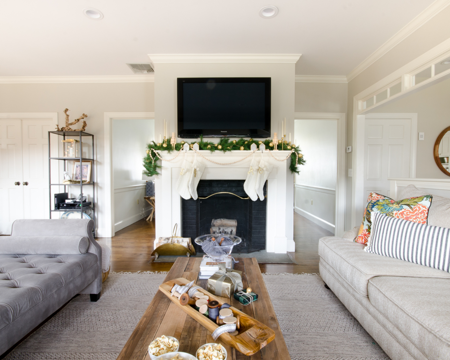 A simple and classic Christmas mantle with greenery, white cable knit stockings, nutcrackers, and gold accents. 2017 Holiday Housewalk