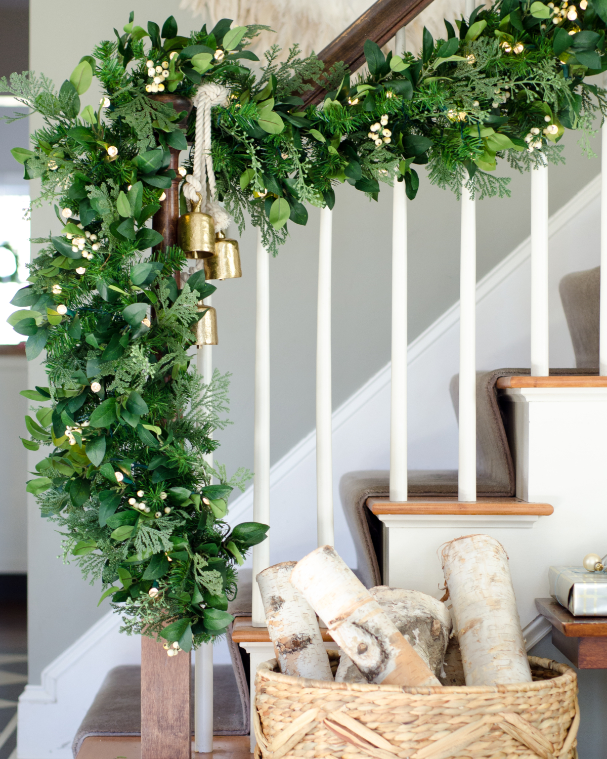 Classic Christmas entry with red, black, white, and greenery. Thick faux garland with white accents.