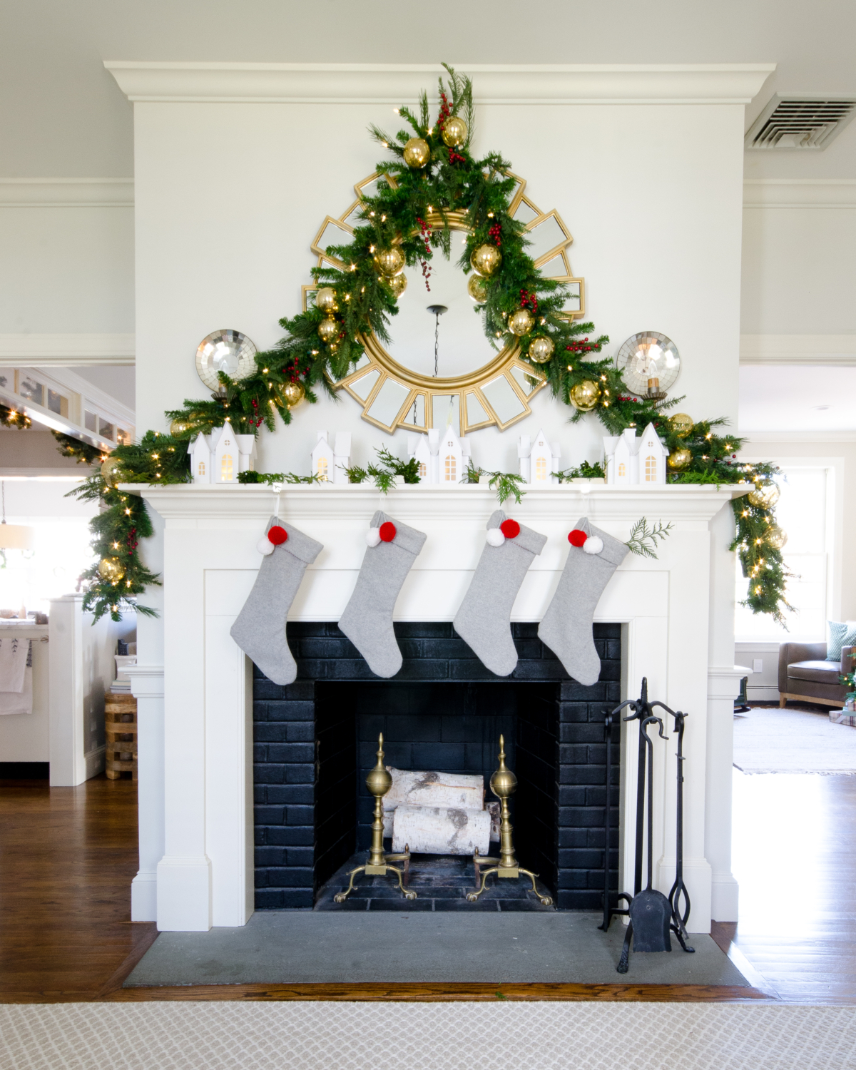 Classic Christmas mantle with lush garland, village houses, white, grey, gold, and red.
