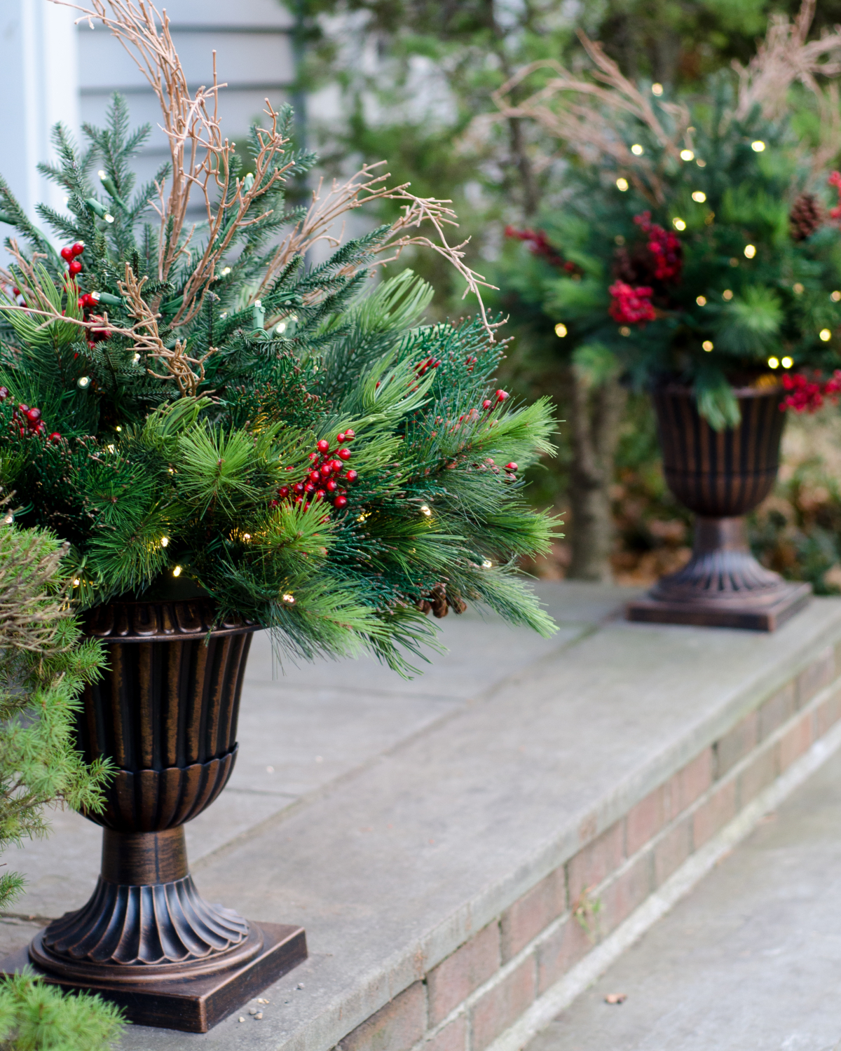 Classic Christmas front door with evergreen wreath and lush urn planters