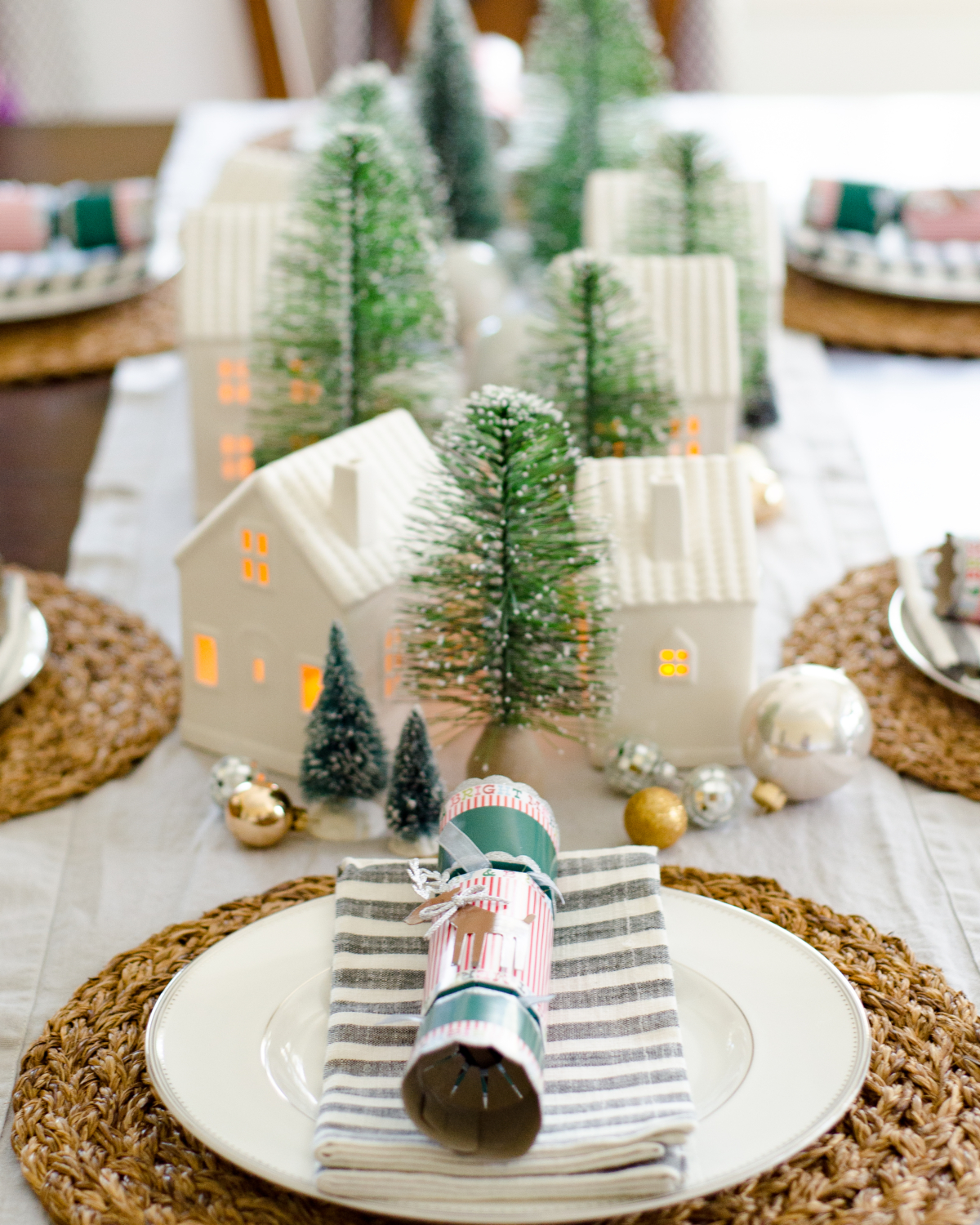 A simple and classic Christmas dining room with ceramic houses and bottle brush trees used as a Christmas centerpiece idea.
