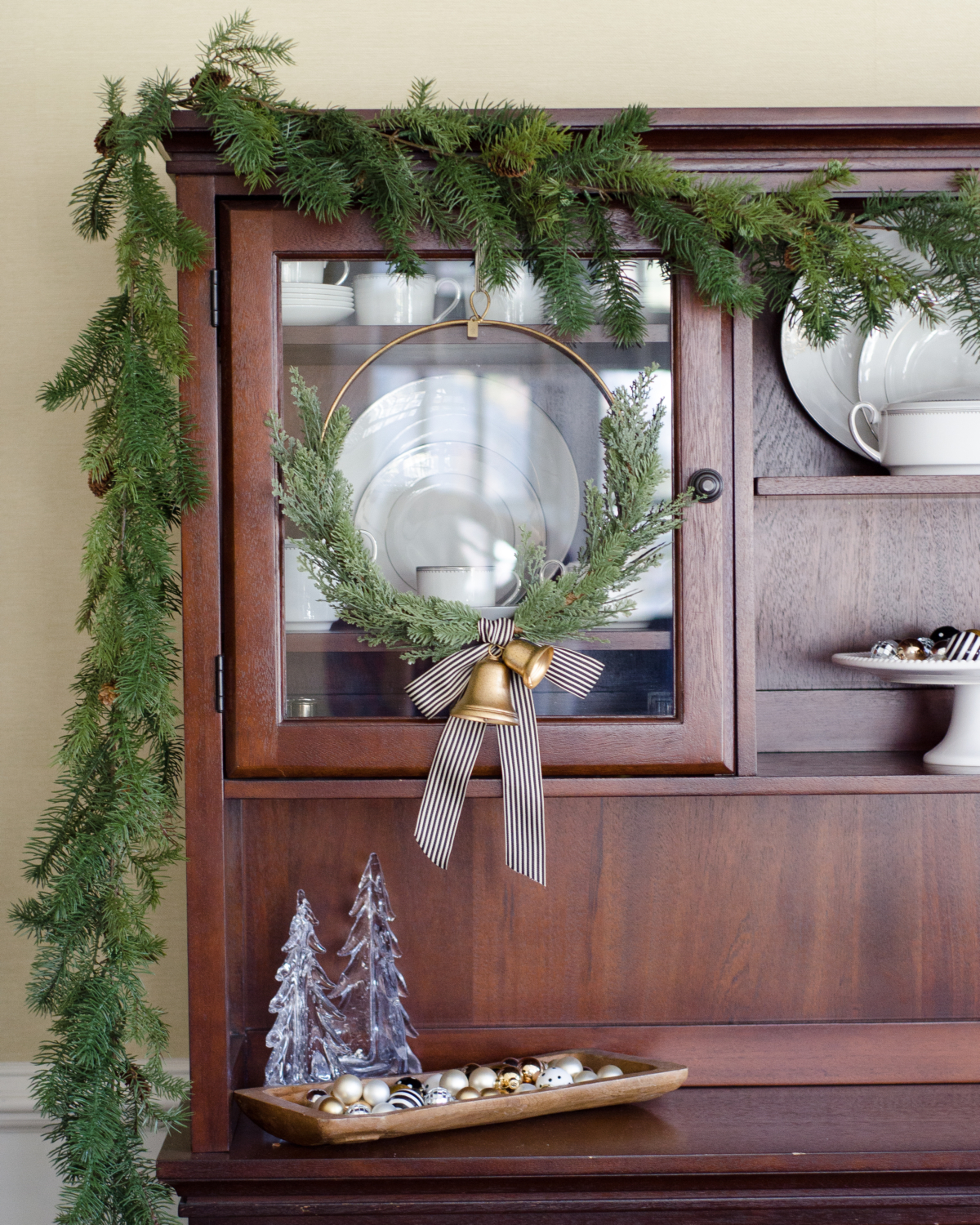 Simple greenery and gold bells on a Christmas hutch in the dining room