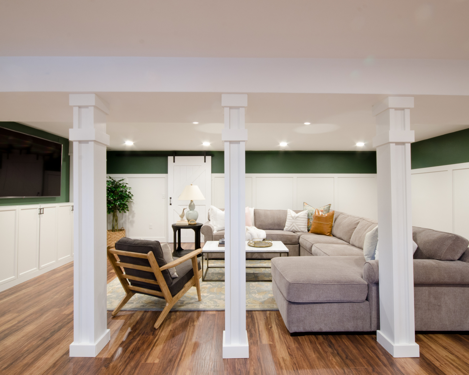 How to turn support poles into columns - an easy to follow tutorial showing how to cover basement support poles with simple building materials so they become stately columns. Just the extra polish a finished basement family room needs to make it feel less like a basement!