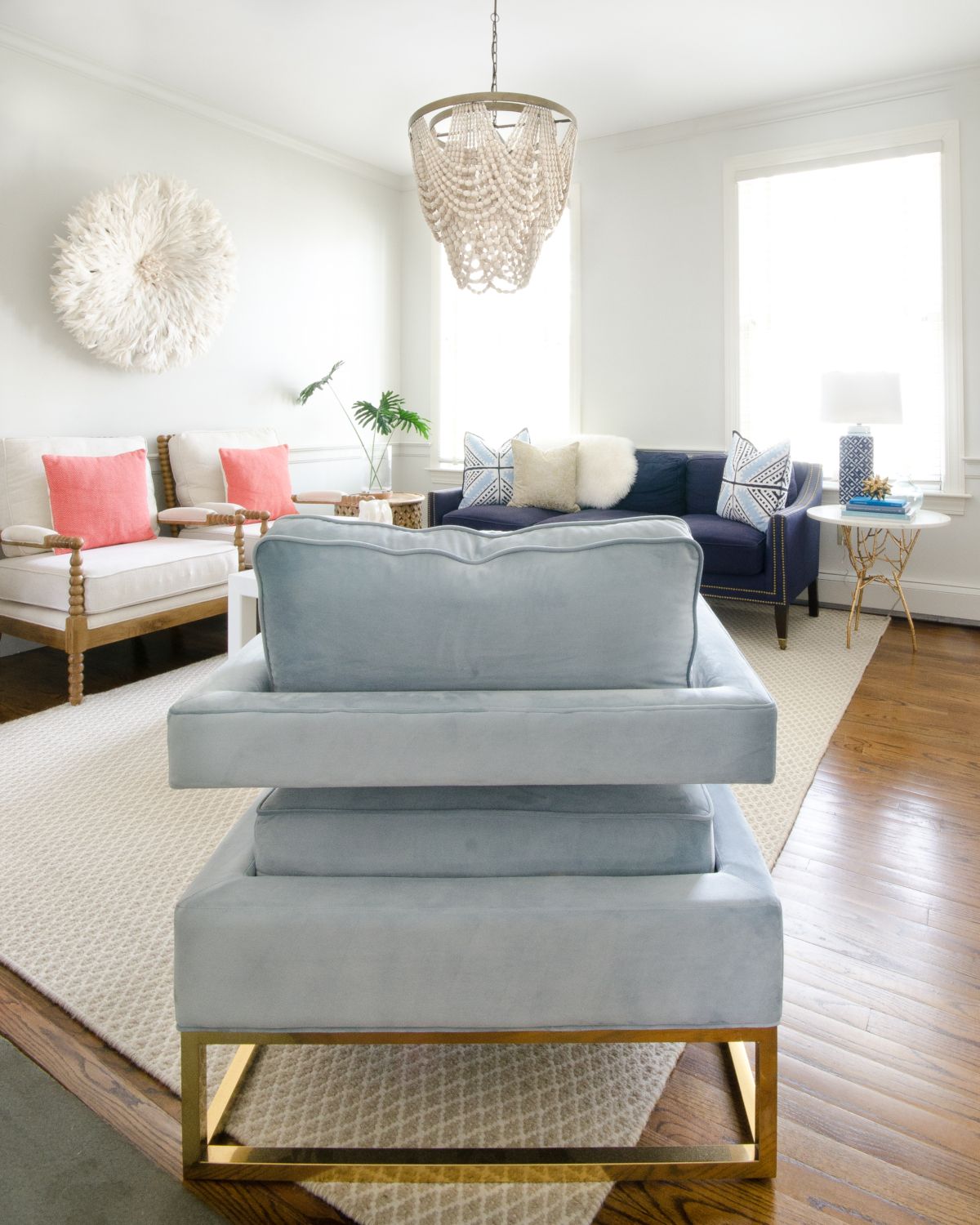 Classic living room design with a slight boho spin. A simple palette of blue, white, and coral keeps the room feeling soft and neutral with a just a bit of color. A draped beaded pendant light is the centerpiece of the room and a total showstopper.