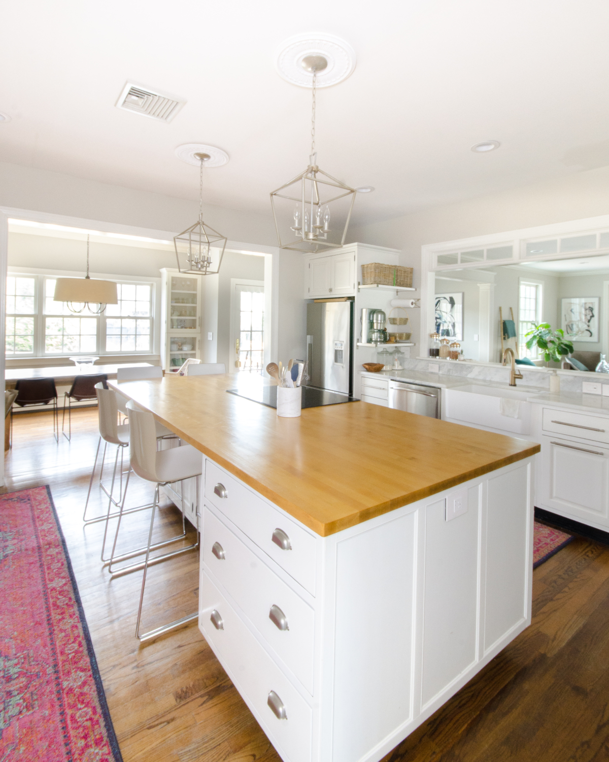 A classic white kitchen with lantern kitchen pendants and warm wood accents. Beautiful mix of traditional and modern in this family-friendly kitchen.