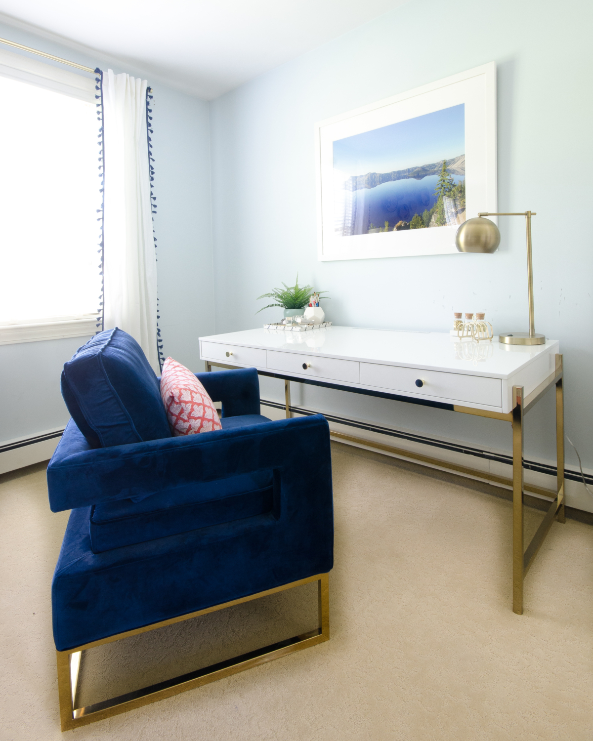 Glam desk area with blue velvet chair and white lacquered with brass accents